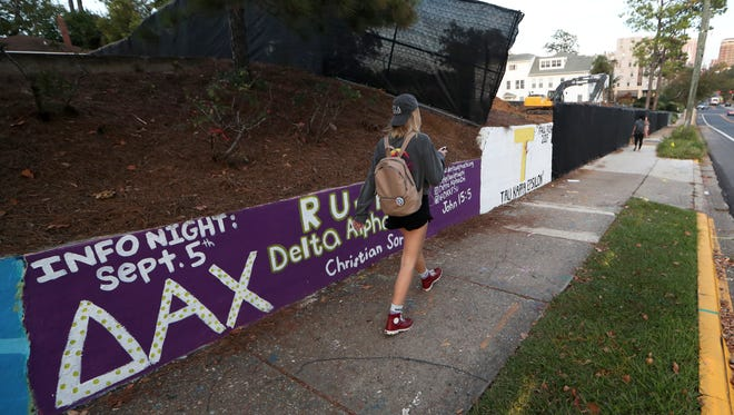 A student walks by a sorority's mural on FSU campus, one day after the university officially halted Greek life activities following the death of a student at an off-campus party.