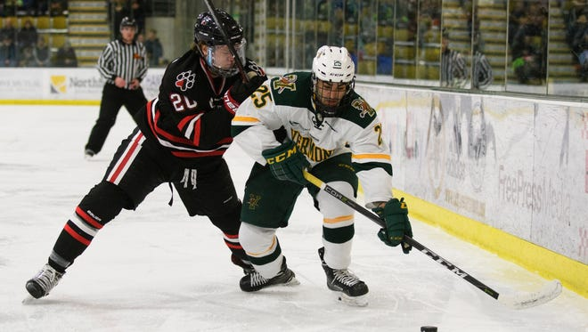 Vermont forward Matt Alvaro (25) skates past Northeastern's Eric Williams (20) with the puck during the men's hockey game between the Northeastern Huskies and the Vermont Catamounts at Gutterson Fieldhouse on Friday night February 16, 2018 in Burlington.