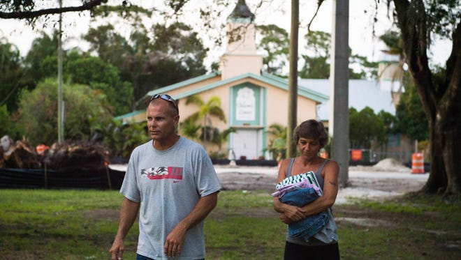 """Michael Parsons and his wife, Jennifer Parsons, walk to his mother's house from their house, which is across the street from the Islamic Center of Fort Pierce in White City. Michael Parsons said he's been concerned in the past over people targeting the mosque, seen behind him, but there are several churches on the block, and the mosque has the same right to be there as any place of worship. """"Nothing bothered me until someone lit (the mosque) on fire next to my house in the middle of the night,"""" he said."""