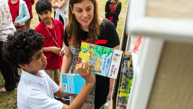 Petway Elementary Vice Principal Jaclyn Mongelluzzo and fifth grader Victor Fernandez fill the new book share box at Giampietro Park on Monday, June 5.