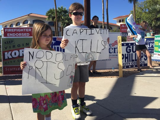 Emilia James, 4, and Max James, 6, hold up signs they