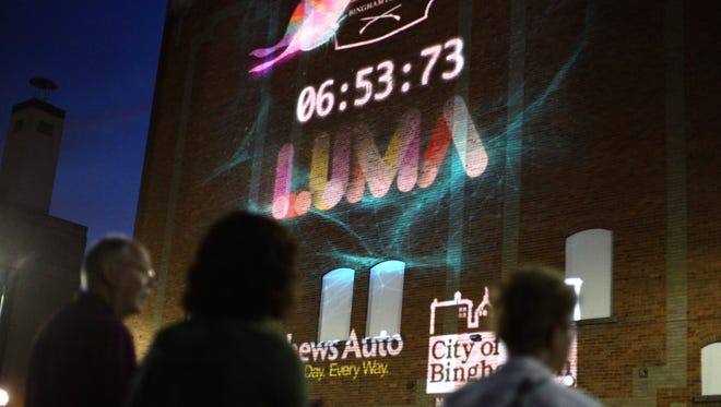People gather along State Street in downtown Bighamton before the beginning of LUMA, a projection art festival in 2016.