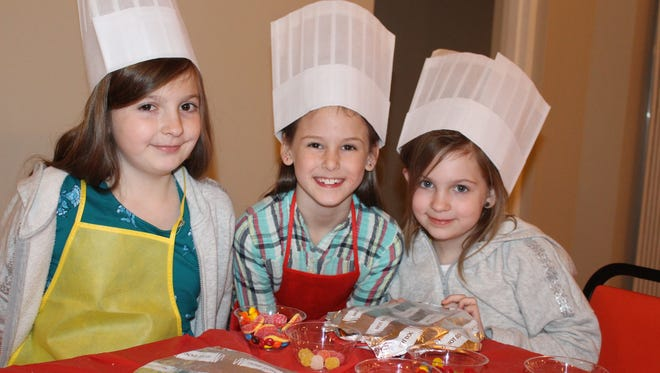 """Abby Simpson, 10, Kate Capps, 8, Claire Simpson, 8, earned a junior chef hat at the """"Nature's Candy Store,"""" workshop presented by Memphis Botanic Garden and Lakeland Parks and Recreation. The junior bakers created a take-home candy pizza at the event."""