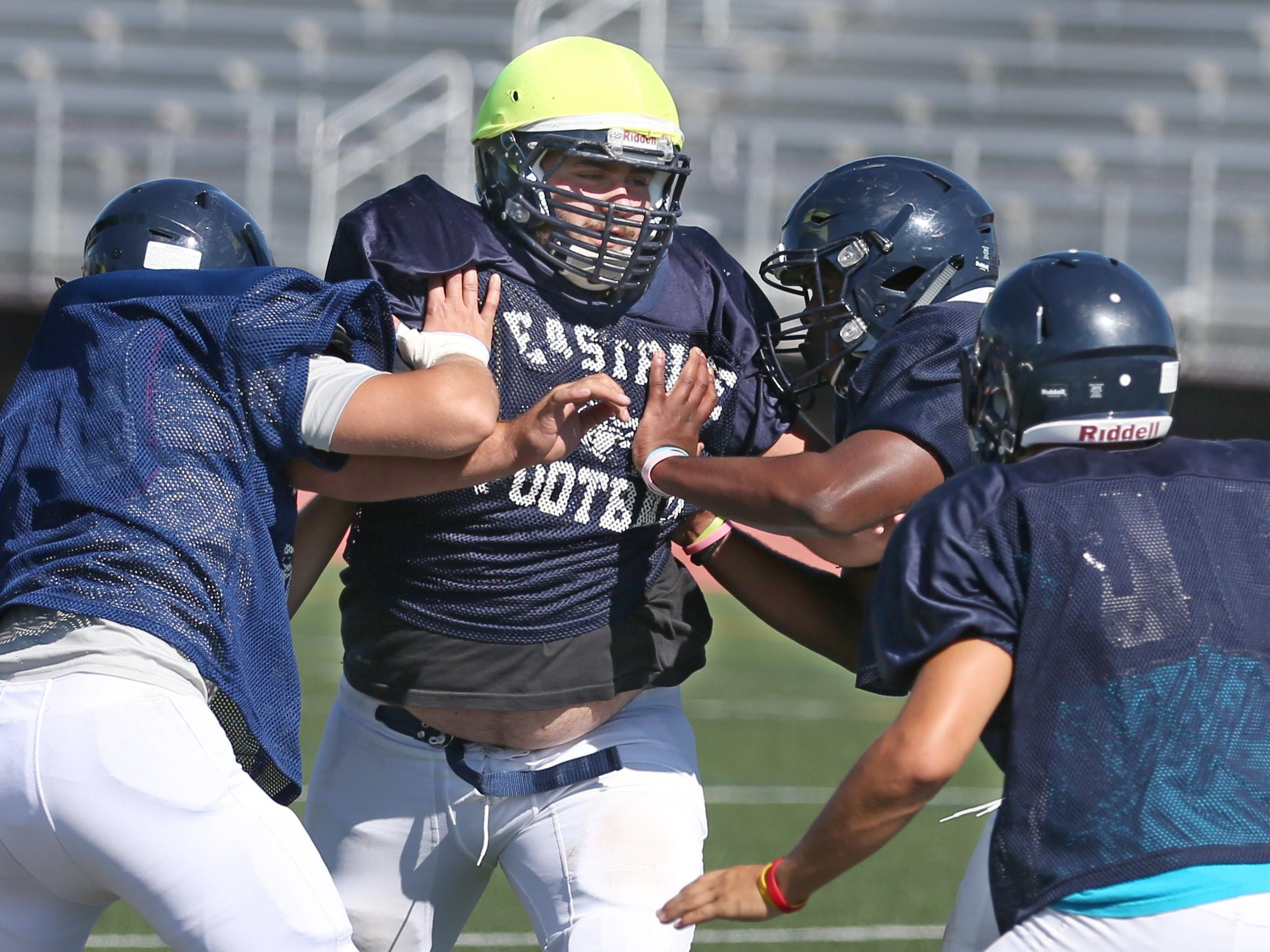 Joe Capuano, DL/OL, power rushes through three defenders to put pressure on the ball during kickoff drills during practice at Eastridge High School in Irondequoit on Monday. Eastridge is the eighth stop on the Democrat and Chronicle's high school football camp tour.