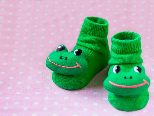 Pair of green child socks with frogs toys closeup