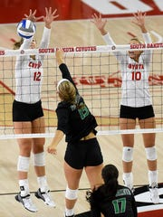 USD's Elizabeth Loschen (12) and Lindsey Brown (10) go up for a block against UND's Faith Dooley during their game at the Sanford Coyote Sports Center on Tuesday in Vermillion.