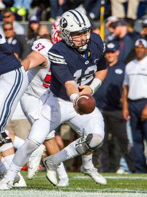 Brigham Young quarterback Tanner Mangum (12) hands off the ball during Saturday's game against Southern Utah in Provo, Utah, Nov. 12, 2016.