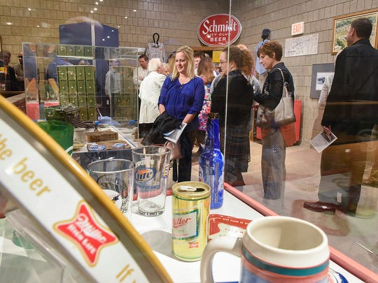 People looked at the Bernick's display during a 100th anniversary reception Tuesday, April 26, 2016, at the Stearns History Museum.