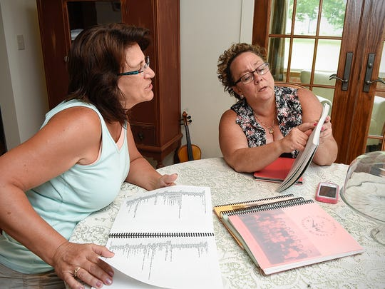 Cousins Bridget Britz and Penny Buch describe their family history from Jacob and Rose Girtz on Thursday, July 6, in Pierz. The family is gathering for a reunion that happens every four years.