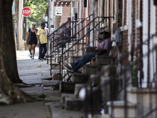 Residents walk through the 900 block of N. Church St.
