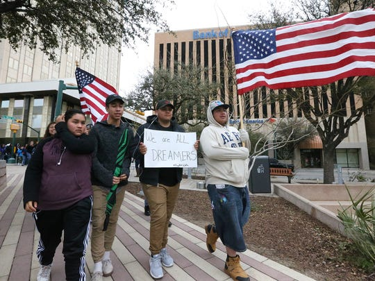 Young people carry U.S. flags as they walk into San Jacinto Plaza during a Dreamers Rally Sunday in downtown El Paso.