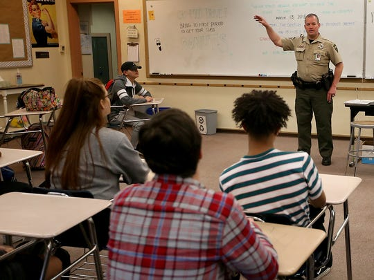 Kitsap County Sheriff's Department's Mark McVey talks with students after observing their ALICE drill at Central Kitsap High School in Silverdale on Tuesday, March 13, 2018.