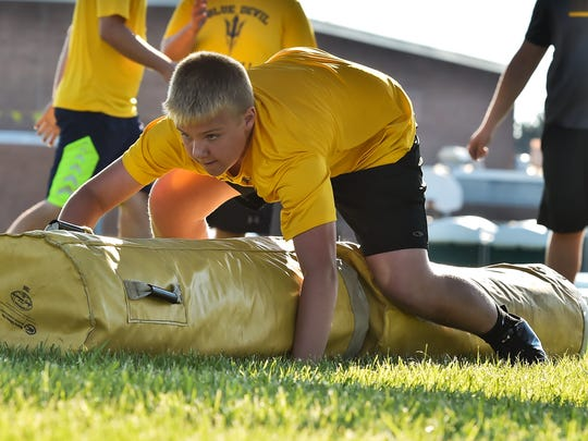 Greencastle's Chase Remserg bear crawls during a lineman challenge at Kaley Field in Greencastle, Pa. on Wednesday, June 29, 2016.