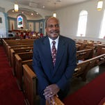 Rev. Reginald Davis poses in the sanctuary of the First Baptist church  in Williamsburg, Va.