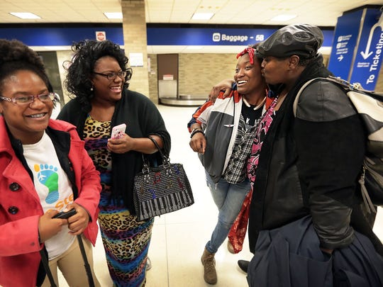 Sonja Coppage (right) welcomes her daughter Ayana Coppage home at the Memphis International Airport after a trip to Africa with Chiquirra Madkins (left) and a group of kids from the One Step Initiative. The youth ambassadors were returning from a two-week trip to Ghana where they learned about the country and its culture.