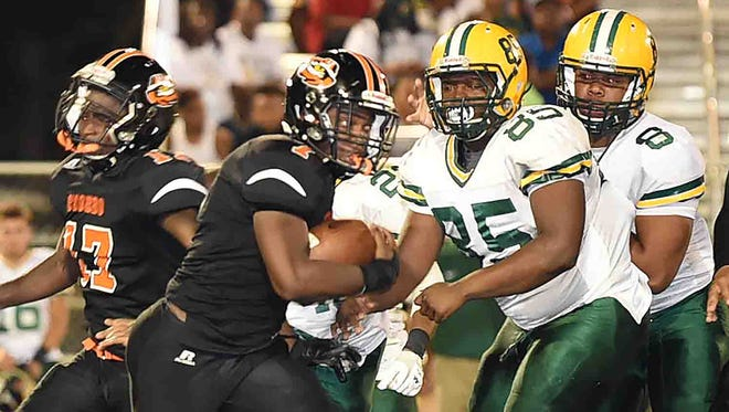 Opelousas High running back Kenny Frazier (1) tries to get around Cecilia defensive end Dominique Prejean (85) during the Bulldogs' District 5-4A win Thursday at Donald Gardner Stadium in Opelousas.