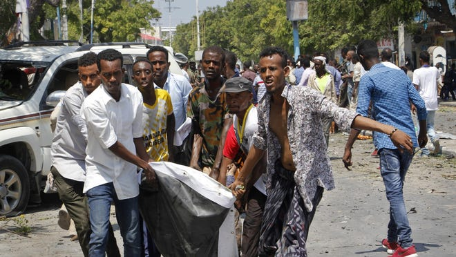 Somalis carry a man who was wounded after a blast outside a restaurant in Mogadishu, Somalia, Thursday, March 28, 2019. A Somali police officer says an explosives-laden vehicle has detonated.