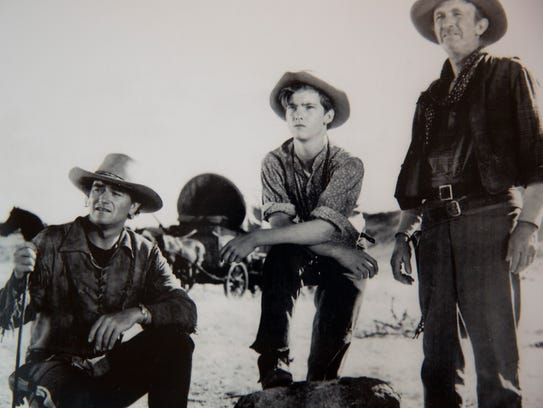 Mickey Kuhn, center, alongside John Wayne, left, and