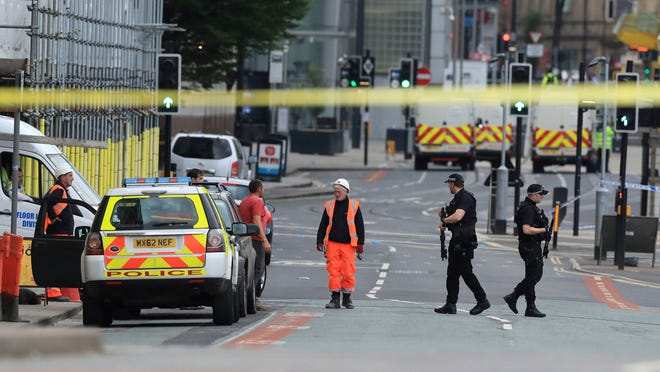 Police guard close to the Manchester Arena in Manchester, Britain, Tuesday May 23, 2017, a day after an explosion. An apparent suicide bomber set off an improvised explosive device that killed over a dozen people at the end of an Ariana Grande concert, Manchester police said Tuesday. (Peter Byrne/PA via AP)