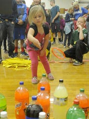 Alexa Palmer, 4, plays a ring toss game at the festival.