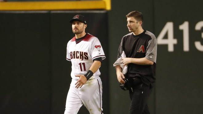 Arizona Diamondbacks center fielder A.J. Pollock (11) is taken out of the game by head athletic trainer Ryan DiPanfilo after an injury diving for a ball against the Milwaukee Brewers during the ninth inning at Chase Field in Phoenix, Ariz. May 14, 2018.