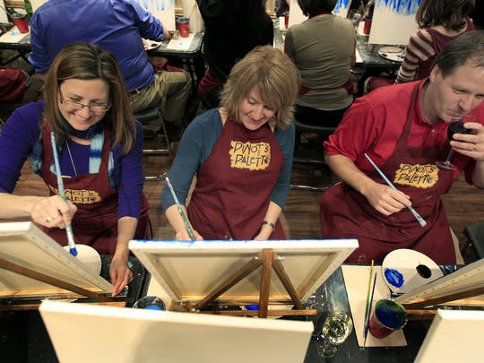 From left, Amy Votsers, Vicki Van Epps and Mike Ray paint a night landscape during a painting party at Pinot's Palette in Appleton. The mixing of painting, wine and a night out is a popular trend as people seek new entertainment options.