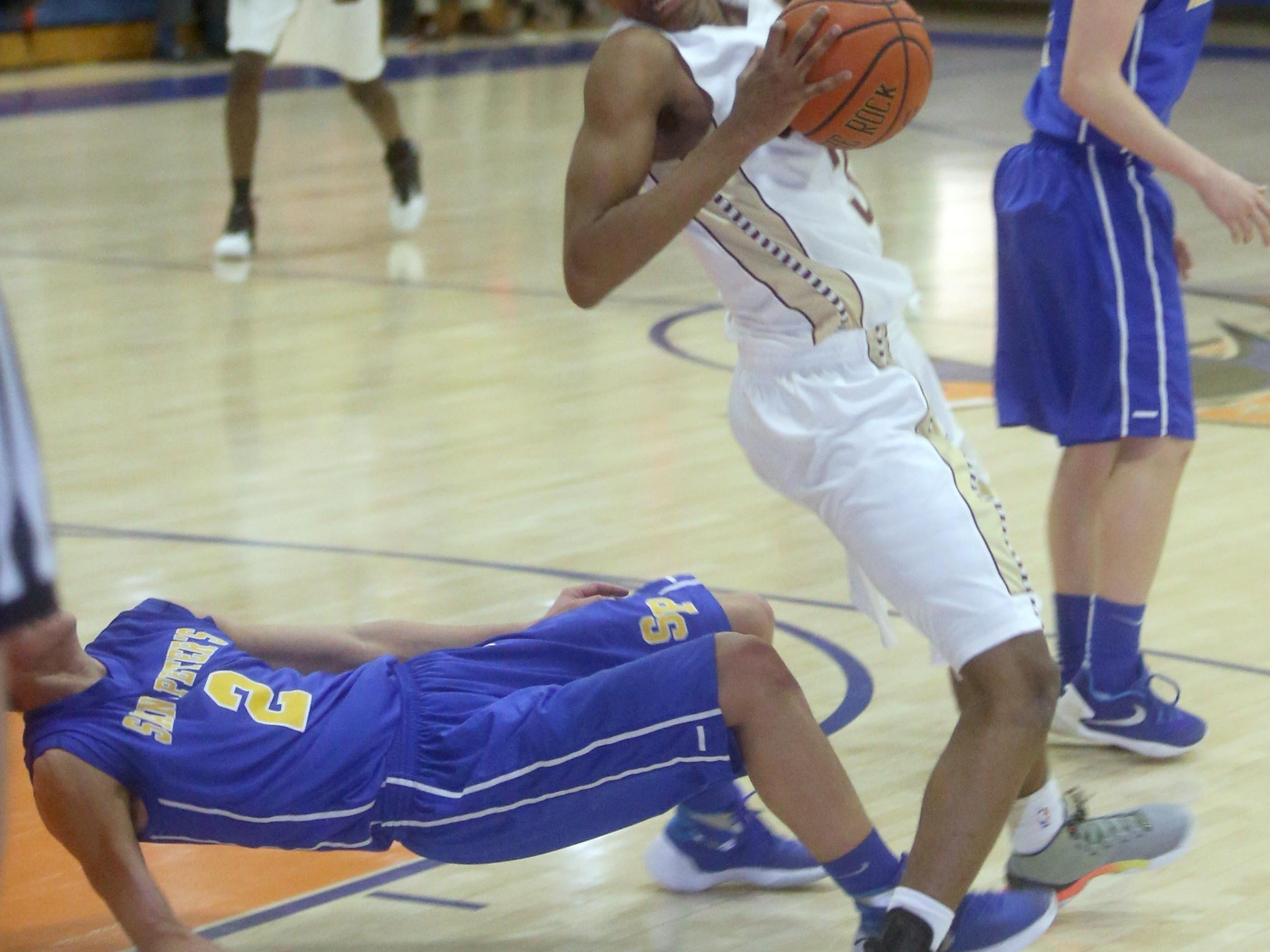 St. Peter's Dylan Walsh goes down while defending Iona Prep's Bryce Wills during a CHSAA second round AA playoff basketball game against St. Peter's at St. Raymond High School in the Bronx March 3, 2016. Iona Prep defeated St. Peter's 51-43.