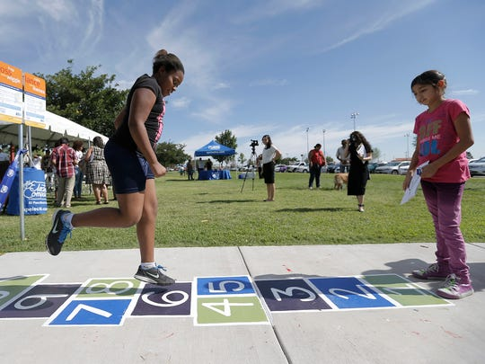 Journey Davis, 10, plays hopscotch after the ribbon was cut to officially open the Born Learning Trail at Veterans Park in Northeast El Paso.