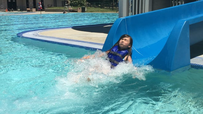 Tara Reuck, 8, slides into the water at the Redding Aquatic Center for relief from the heat Friday while visiting town to see her grandmother, Mia McKee, and great-grandmother Linda Carter. The city pool will reopen to the public Monday following a weekend swim meet.