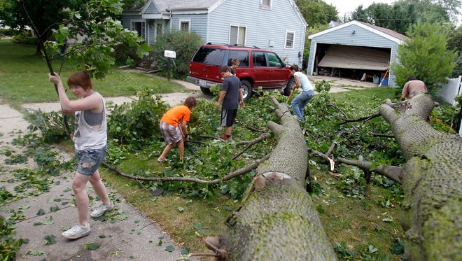 A joint effort helps clean up a Kimberly yard on after a fast-moving overnight storm passed through the Fox Cities.