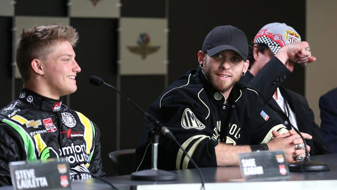 Brantley Gilbert, center, talks to the media, flanked by driver Sage Karam, left, and record company executive Scott Borchetta (with hand raised to show off an Indianapolis 500 Winner's Ring).
