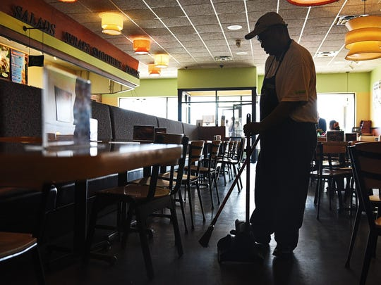 Dung Luong, a Camille's Sidewalk Cafe employee, sweeps Thursday, April 14, 2016 at Camille's Sidewalk Cafe in Sioux Falls.