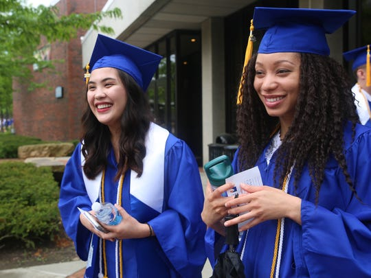 Pleasant Valley resident Audrey Dizon (left) and Hopewell Junction resident Jessica Jackson prepare to walk through campus on Sunday. SUNY New Paltz conferred degrees to nearly 2,000 students this weekend.