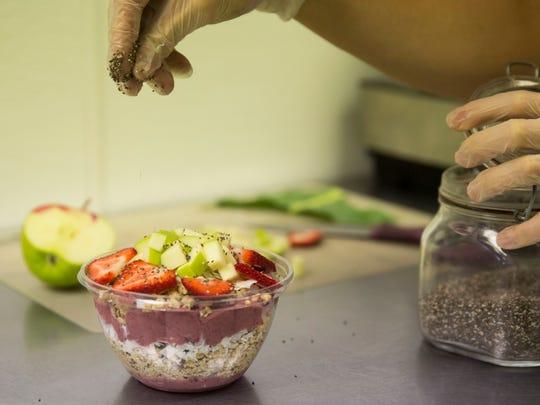 Ryan Perez prepares a smoothie bowl for a customer