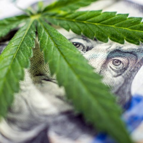 A cannabis leaf lying atop a hundred dollar bill,...