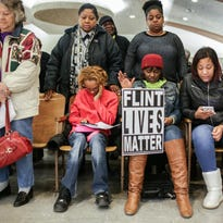 """Ryan Garza/Detroit Free PressFlint resident Dominique Strong holds her hand up while holding a """"Flint Lives Matter"""" sign during a prayer before the start of a Flint City Council meeting about residents' water bills on Monday in Flint City Hall. Flint resident Dominique Strong holds her hand up while holding a Flint Lives Matter sign in her boot during a prayer before the start of a Flint City Council meeting about residents' water bills on Monday February 8, 2016 at the Council Chambers in Flint City Hall."""