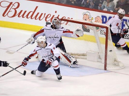 Winnipeg Jets' Tyler Myers (57) scores on Washington Capitals goaltender Braden Holtby (70) with Dmitry Orlov (9) in front of the net during overtime in an NHL hockey game Tuesday, Feb. 13, 2018, in Winnipeg, Manitoba. (Trevor Hagan/The Canadian Press via AP)