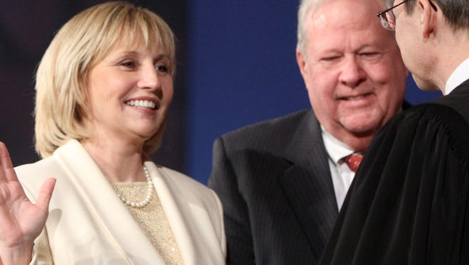 Lt. Gov. Kim Guadagno is sworn into office by Chief Justice Stuart Radner as her husband, Michael Guadagno, looks on.