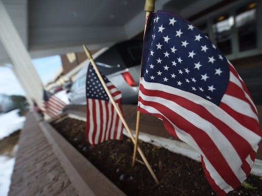 A dozen flags were placed outside of Geigle Funeral Home in Harrisburg in honor of US Marshall Christopher David Hill, who was killed in the line of duty Jan. 18.