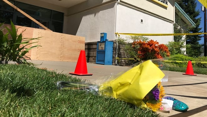 Flowers sit outside Tri Counties Bank in Shasta Lake on Saturday where a day earlier a woman was hit by a vehicle and later died. The vehicle also struck the bank's walk-up ATM on the east side of the building off Shasta Dam Boulevard.