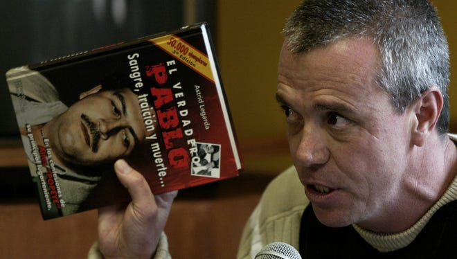 """In this  June 27, 2006, file photo, John Jairo Velasquez, a former hit man for Pablo Escobar, gives his testimony while holding a book titled """"The True Pablo, Blood, Treason, and Death,"""" during the trial against Alberto Santofimio Botero in Bogota, Colombia."""