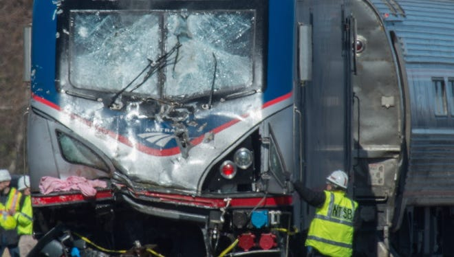 A National Transportation Safety Board staffer inspects the engine of Amtrak Train 89, which hit a construction vehicle on the tracks and derailed in Chester, Pa., on April 3, 2016.