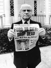 """New York Mayor Abe Beame stands in front of Gracie Mansion holding the New York Daily News front page from Oct. 30, 1975: """"Ford to City: Drop Dead."""" He then said, """"This could never happen with President Carter,"""" and tore up the paper."""