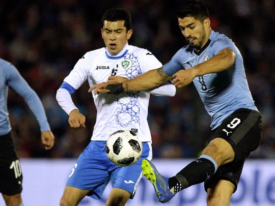 Uruguay's Luis Suarez, right, fights for the ball with Uzbekistan's Aziz Ganiev during a friendly.
