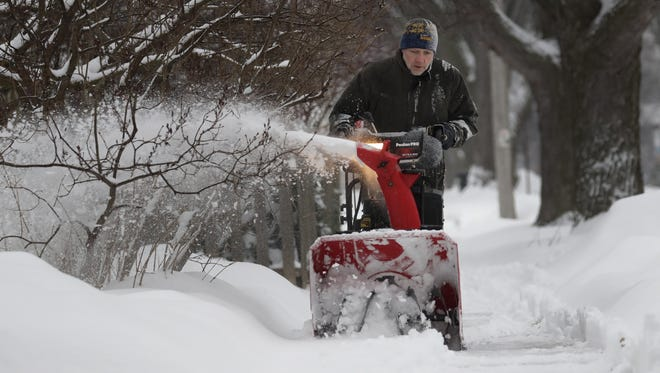 Tim Peterson clears snow from his sidewalk along North Union Street on Tuesday in Appleton.