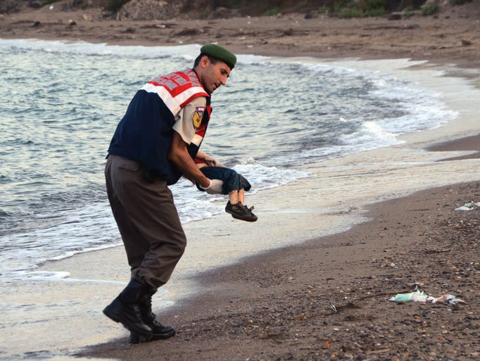 The body of Aylan Kurdi, 3, is carried by a paramilitary
