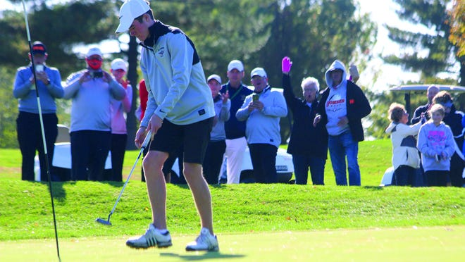 Macomb's Jack Lockard sinks a putt to end his round on Monday at Kellogg Golf Course as his Bomber teammates and Macomb fans react.