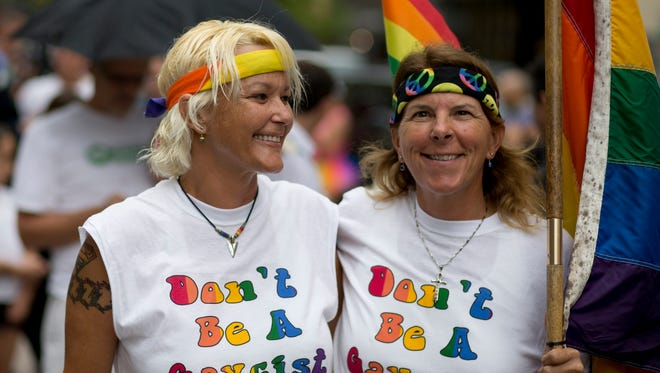 FILE - In this July 2, 2014, file photo, Kimmy Denny and her partner, Barb Lawrence of Palm Harbor, Fla., wait outside a court hearing on gay marriage in Miami. Few of Florida's 67 clerks of court plan to issue marriage licenses to gay couples on Jan. 6, 2015. Several are paralyzed by uncertainty over what to do on the day a federal judge says marriage licenses can be issued in Florida. (AP Photo/J Pat Carter, File)