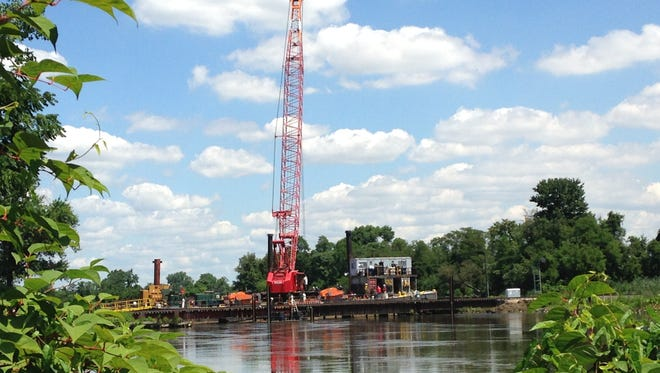 Crews drive pilings into Mantua Creek to build a new rail bridge to replace the old swing bridge.