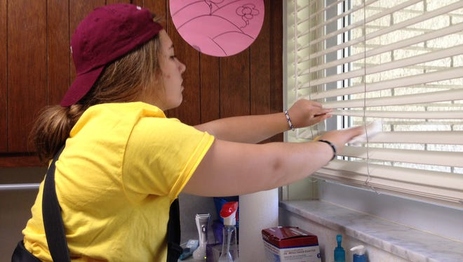 Junior Alana Sullivan cleans blinds in the laundry room as part of Make a Difference Day for Mercy High School students.